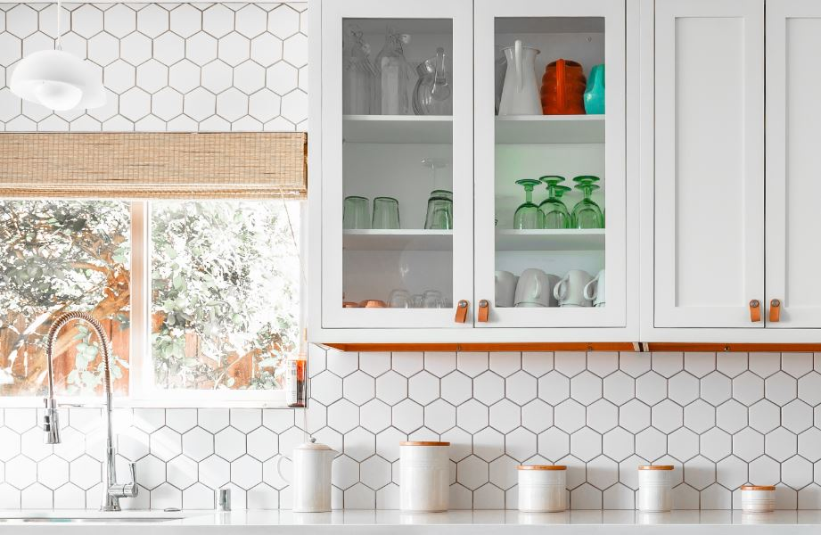 White octagonal decorative tiles in a kitchen with white cabinets that have leather handles