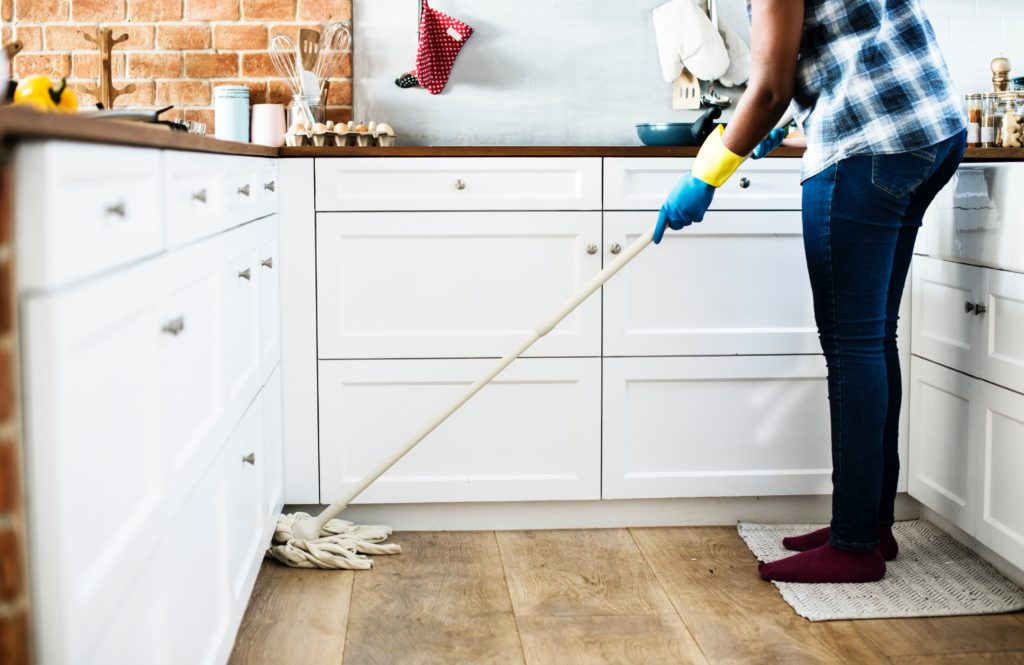 person cleaning floor at home with mop