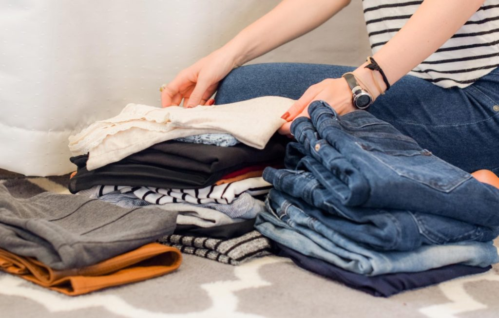 Woman sitting down on rug neatly folding clothes in three piles